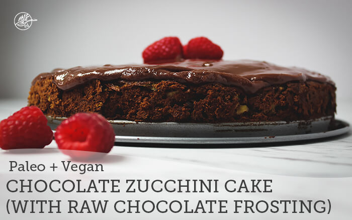 chocolate zucchini cake with chocolate icing and rasberries on white marble table