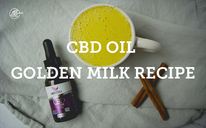 cbdoil bottle with golden milk in mug and cinnamon sticks on table