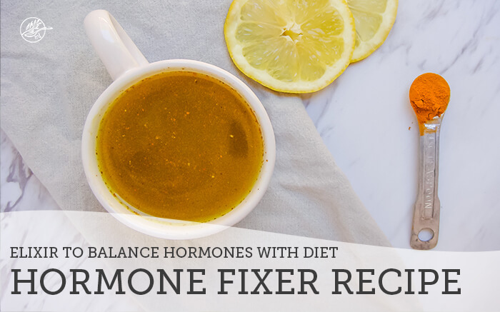 hormone fixer elixir in white mug on table with lemon slices and teaspoon of spice